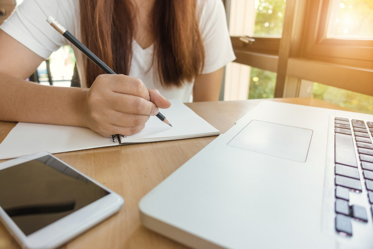 Woman sitting at desk writing with tablet and laptop. Running a six-figure business - is it right for you? Jessica Fearnley Business Consulting. Business Coach.